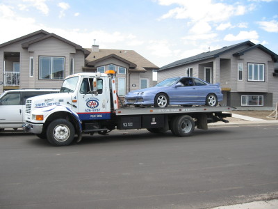 Car on a towing truck representing Auto Spa Towing Ltd.