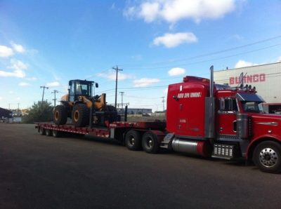 Tractor on landoll truck towing representing Auto Spa Towing Ltd.